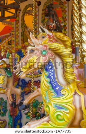 Brightly painted wooden horse called Gemma on fairground ride. - stock photo