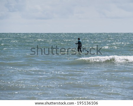 BRIGHTON, EAST SUSSEX/UK - MAY 24 : People paddle boarding at Brighton East Sussex on May 24, 2014. Unidentified man.