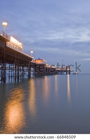 Brighton England pier with beautiful sunset in Winter and lights reflected in sea
