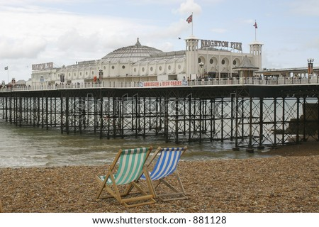 Brighton Pier with 2 empty deck chairs in the foreground - stock photo