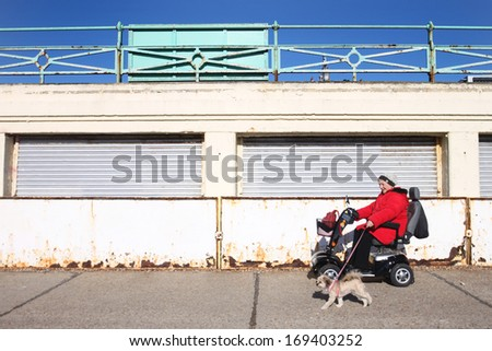 BRIGHTON, UNITED KINGDOM - FEB 2: Disabled woman in electric chair with her dog on February 2, 2011 in Brighton, United Kingdom. Brighton seafront has access ramps for disabled people in wheel chairs. - stock photo