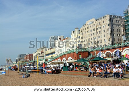 Brighton, United Kingdom - September 28, 2014: A busy lunchtime crowd on a summer day at the restaurants on Brighton Beach. - stock photo