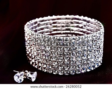 brilliant bracelet and earrings at the dark textile - stock photo