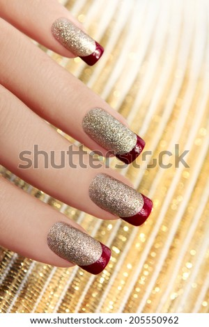 Brilliant Golden manicure with red lacquer on the end of the nail. - stock photo