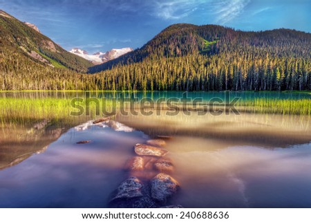 Brilliant mountain lake flanked by evergreen trees with interesting rocks in the foreground - stock photo
