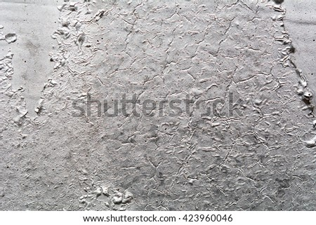 Brilliant silver metallic surface with cracks and fissures.