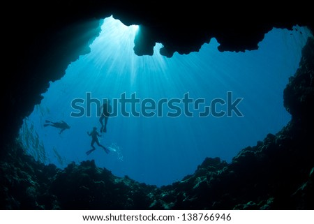 Brilliant sunbeams silhouette snorkelers at the top of a submerged sinkhole in Palau, Micronesia.  Palau is known for its high marine diversity and wonderful diving. - stock photo