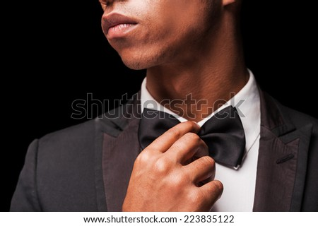 Bringing the bow tie back in style. Fashionable young Afro-American man correcting his bow tie - stock photo