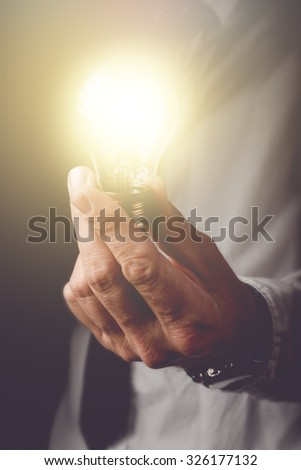 Bringing up the new ideas to company, businessman with light bulb offering new solutions to understanding problems in business, retro toned image, selective focus. - stock photo