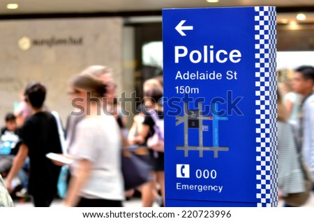 BRISBANE, AUS - SEP 25 2014:Australian people pass by Police Station sign.Gold Coast police on high terror alert warned to be hyper vigilant and patrol local mosques and critical infrastructure sites - stock photo
