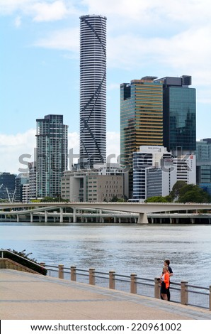 BRISBANE, AUS - SEP 25 2014: Couple under the skyline of infinity Tower. The Infinity Tower is a 249-metre (817 ft) skyscraper by Meriton. Infinity Tower is the tallest building in Brisbane today. - stock photo