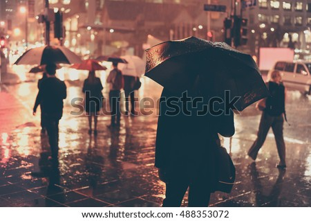 BRISBANE, AUSTRALIA - APRIL: Blur silhouette people with umbrella across street at night rain in CBD Brisbane on April, 2015, Brisbane, Australia