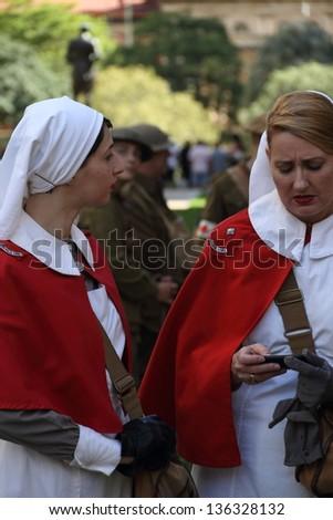 BRISBANE, AUSTRALIA - APRIL 25 : Unidentified World War 2 reenactors texting during Anzac day commemorations  April 25, 2013 in Brisbane, Australia - stock photo