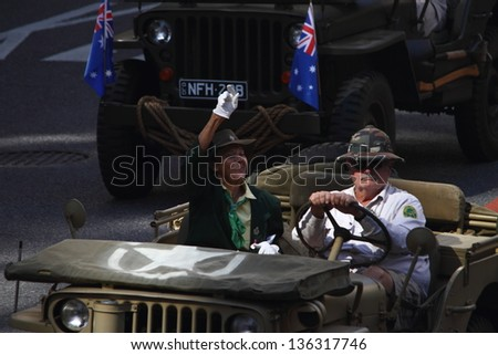 BRISBANE, AUSTRALIA - APRIL 25 : Veteran waves to crowd from jeep  during Anzac day commemorations  April 25, 2013 in Brisbane, Australia - stock photo