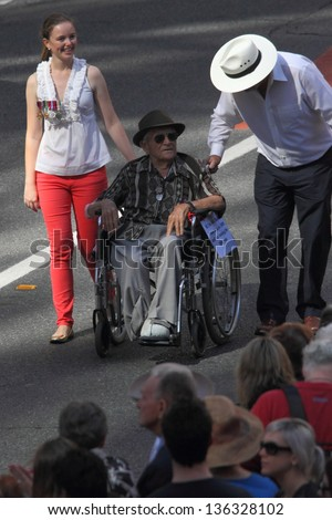 BRISBANE, AUSTRALIA - APRIL 25 : 104 yr old veteran Ken Blake pushed in wheelchair during along march route during Anzac day commemorations  April 25, 2013 in Brisbane, Australia - stock photo