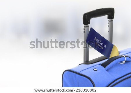 Brisbane, Australia. Blue suitcase with label at airport. - stock photo