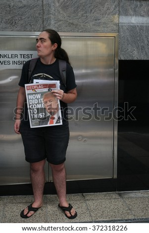 BRISBANE, AUSTRALIA - FEBRUARY 05 : Anti right wing newspaper seller at protest in support of churches offering sanctuary to refugees February 05, 2016 in Brisbane, Australia - stock photo