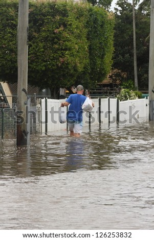 BRISBANE, AUSTRALIA - JANUARY 28 : Unidentified resident taking groceries through flood waters from ex tropical cyclone Oswald on January 28, 2013 in Brisbane, Australia - stock photo