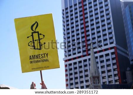 BRISBANE, AUSTRALIA - JUNE 20: Amnesty International placard at World Refugee Day Rally June 20, 2015 in Brisbane, Australia - stock photo