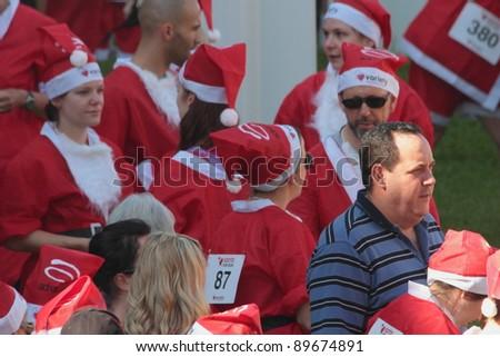 BRISBANE, AUSTRALIA  NOV 27 :Spectator mixes with unidentified group pre Variety Santa Fun Run November 27, 2011 in Brisbane, Australia - stock photo