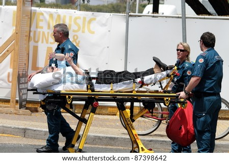 BRISBANE, AUSTRALIA  OCT 24 : An unidentified woman is given medical attention in the heat during the English Royal visit on October 24, 2011 in Brisbane, Australia - stock photo
