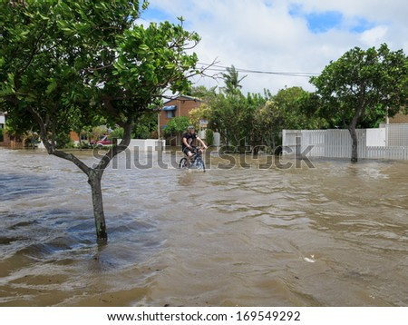 BRISBANE, QLD, AUSTRALIA - January 27: A man cycles through the flooded streets in Brisbane during the floods in January 27, 2013 - stock photo