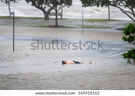 BRISBANE, QLD, AUSTRALIA - January 27: Man lies in flood water in Brisbane, during the floods of 27 January 2013 - stock photo