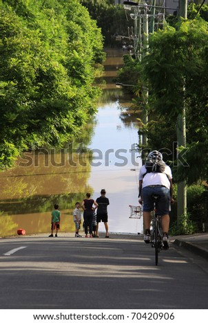 BRISBANE, QUEENSLAND/AUSTRALIA - JANUARY 13: Bicycle driver rides to a flooded street 13, 2011 in Milton, Brisbane, Queensland, Australia. - stock photo