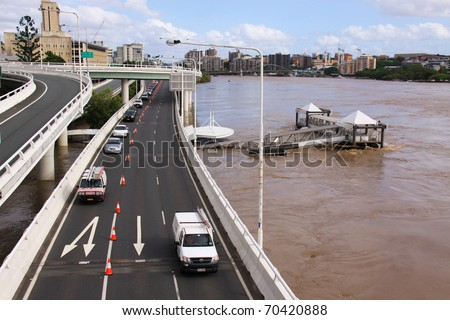 BRISBANE, QUEENSLAND/AUSTRALIA - JANUARY 13: Cars driving over bridge with destroyed City Cat pontoon on January 13, 2011 in Toowong, Brisbane, Queensland, Australia. - stock photo