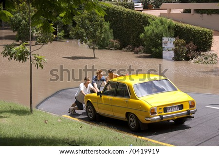 BRISBANE, QUEENSLAND/AUSTRALIA - JANUARY 13: People pushing a car out of the water on January 13, 2011 in St Lucia, Brisbane, Queensland, Australia. - stock photo