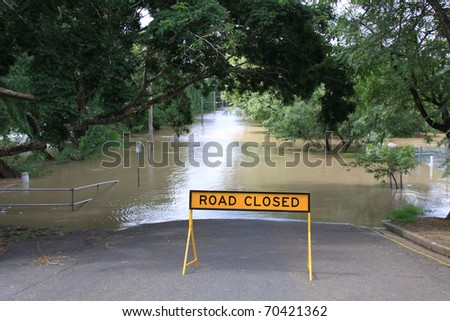 BRISBANE, QUEENSLAND/AUSTRALIA - JANUARY 13: Road closed sign in front of a flooded street on January 13, 2011 in Toowong, Brisbane, Queensland, Australia. - stock photo