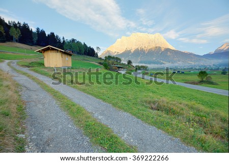 Brisk autumn scenery of idyllic Tyrolean countryside in Lermoos, Tirol, Austria, with rugged Zugspitze Mountain in the background and country roads winding on green meadows by the hillside - stock photo