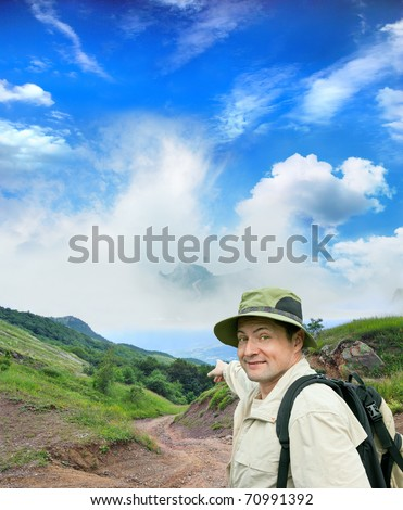 brisk tourist shows the direction on a country road - stock photo