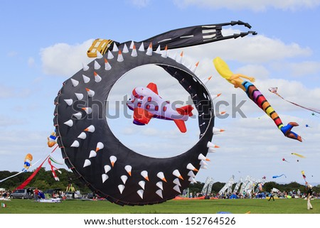 BRISTOL - AUGUST 31: An array of kites including a mermaid, giant spiky bowl and an airplane flying together at the Bristol International Kite Festival, England, August 31, 2013  - stock photo