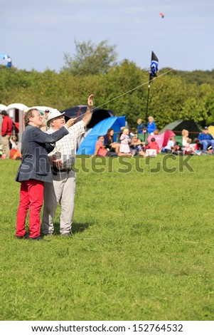 BRISTOL - AUGUST 31: Bristol's elected mayor, George Ferguson takes some kite flying lessons at the Bristol International Kite Festival, England, August 31, 2013  - stock photo