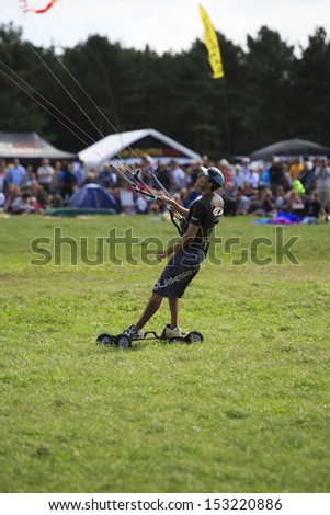 BRISTOL - AUGUST 31: Unidentified man kite skateboarding at the 2013 Bristol International Kite Festival, England, August 31, 2013 - stock photo