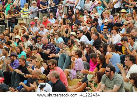 BRISTOL, ENGLAND - AUGUST 2: A happy audience on the Cascade Steps  applauds an act at the annual Harbour Festival in Bristol, England on August 2, 2009. 250,000 people attended the free event . - stock photo