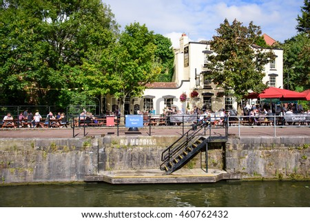 Bristol, England - July 17, 2016: Crowds and customers line the quayside of Bristol's Floating Harbour outside the Ostrich pub.