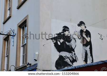 BRISTOL - OCT 23: Stencil graffiti piece by Banksy on a building on Oct 23, 2010 in Bristol, UK. Banksy is an anonymous England based graffiti artist, political activist, film director and painter. - stock photo