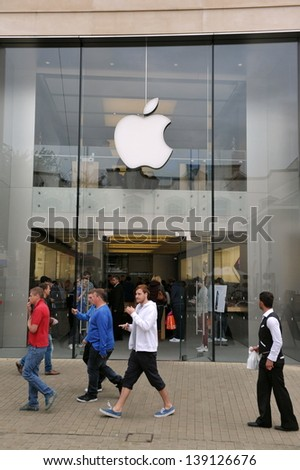 BRISTOL- SEPT 21: Shoppers pass an Apple store as the Iphone 5 is launched in the UK and Europe on Sept 21, 2012 in Bristol, UK. The consumer electronics giant has 394 retail stores in 14 countries. - stock photo
