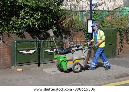 Bristol, UK - March 17, 2011: A street sweeper walks along a city centre road. Bristol City Council employ street sweeping and refuse collection services throughout the west country city.  - stock photo