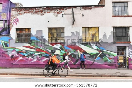 BRISTOL, UK - OCT 31, 2015: People pass graffiti on a building in the city centre. The west country city is famous for its vibrant graffiti and street art.  - stock photo
