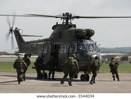 British Army soldiers board helicopters - stock photo