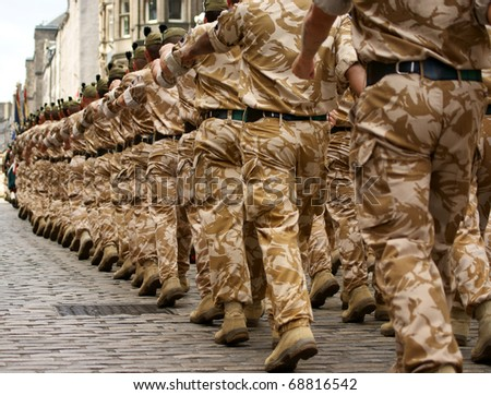 British Army soldiers marching in desert camouflage uniform. - stock photo