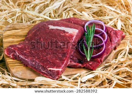 British Beef Flat Iron steak on cutting board and straw, rosemary and onion. - stock photo