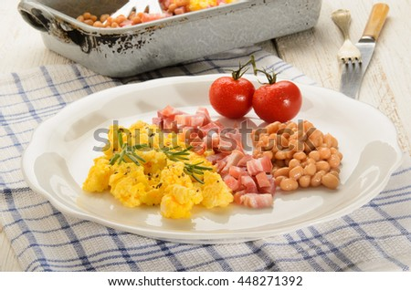 british breakfast with scrambled eggs on a plate, smoked bacon cubes, baked beans, fresh tomatoes, rosemary   - stock photo