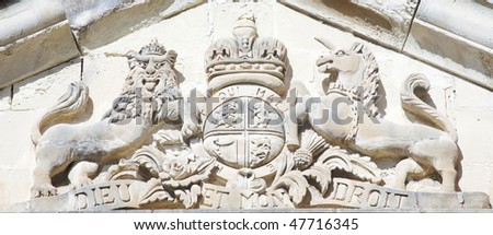 british coat of arms carved out of limestone on the maltese islands - stock photo