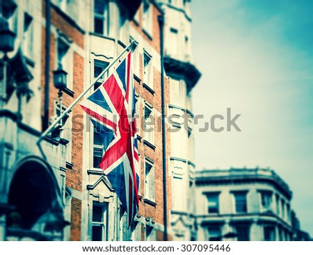 British flag on the building. London, UK. Toned image. Selective focus on the flag and blurred background. - stock photo