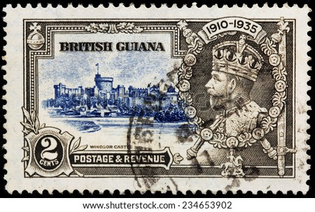 BRITISH GUIANA - CIRCA 1935: A stamp printed by BRITISH GUIANA shows view of Windsor Castle and image portrait of Georg V - King of the United Kingdom and the British Dominions, circa 1935 - stock photo