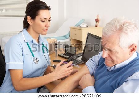 British nurse giving injection to senior man - stock photo